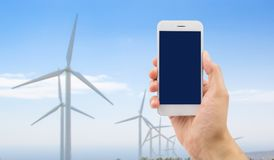 Contact the renewable energy. Hand holding a phone with background wind turbines windmill in concept as contact renewable energy company Stock Photo