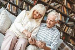 Contact se reposant de smartphone de lecture rapide de couples ensemble à la maison de concept supérieur de retraite Image stock