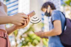 Free Contact Tracing App COVID-19 Pandemic Coronavirus Mobile Application - People Wearing Face Mask Using Smart Phone App In Stock Photography - 184093302