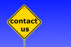 Contact us. Written on a yellow road sign Royalty Free Stock Photos