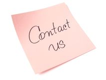 Contact us. Handwritten message on pink sticker Stock Images