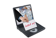 Contact us. A business people hand holding a paper with contact us handwritten concept of receiving a message through a laptop,as if the message was sent from a Royalty Free Stock Photo