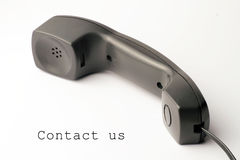 Contact us. Black telephone isolated on a white background with the sign contact us stock photos