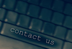 Contact us. Keyboard background with text above Stock Photos