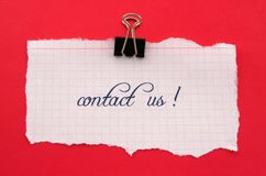 Contact us. Note on red background Stock Images