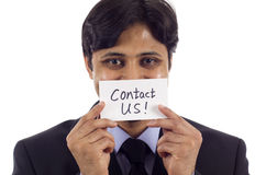 Contact Us!. Smiling Asian business man holding a card- Contact Us! isolated over white background Stock Photo