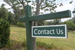 Contact Us. Sign in a beautiful natural setting with the words 'Contact Us Stock Photo