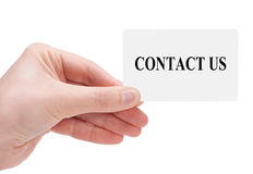 Contact us. Woman's hand with card that say contact us royalty free stock image