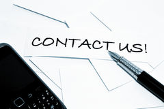 Contact us!. Writing with fountain pen and cell phone Royalty Free Stock Photos
