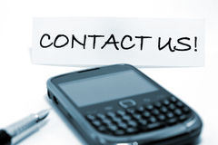 Contact us!. Writing with fountain pen and cell phone Stock Photos