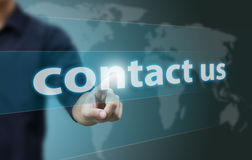 Contact us. Hand pushing contact us button on a touch screen interface Stock Photography