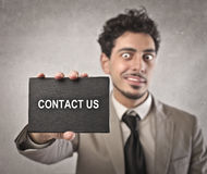Contact Us. Businessman holding a black cardboard on which is written contact us Stock Images