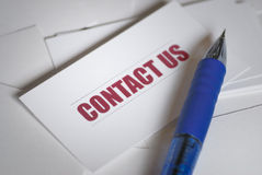 Contact us. Card and blue pen Royalty Free Stock Images
