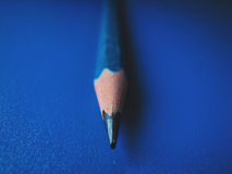 Sharp pencil. A sharp blue pencil on a blue background royalty free stock images