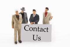 Contact Us. Miniature businessmen with Contact Us sign Stock Image