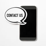 Contact us banner. Contact us text in a speech bubble with a smartphone. Speech balloon cut from cardboard. Information button, icon or banner for website Royalty Free Stock Image