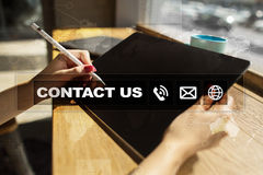 Contact us button and text on virtual screen. Business and technology concept. Stock Photography