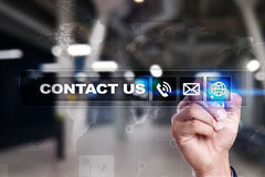 Contact us button and text on virtual screen. Business and technology concept. Stock Photo