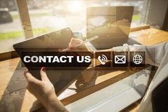 Contact us button and text on virtual screen. Business and technology concept. Royalty Free Stock Image
