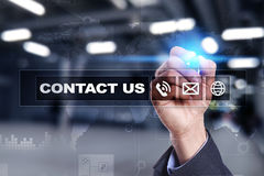 Contact us button and text on virtual screen. Business and technology concept. Royalty Free Stock Photo
