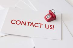 Contact us. Card with miniature telephone stock photo