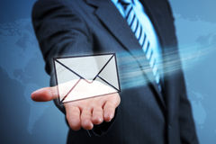 Contact us by e-mail. Businessman holding a virtual envelope concept for e-mail, global communications, mail or contact us Stock Photos