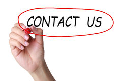 Contact us. Holding a red pen and drawing a circle on white background. Showing Contact Us royalty free stock photo