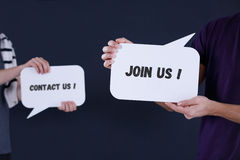 `Contact us` and `Join us` speech bubbles. Two people holding `Contact us` and `Join us` speech bubbles Stock Image
