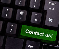 Contact us on keyboard. Keyboard with green button, spelling contact us Stock Images
