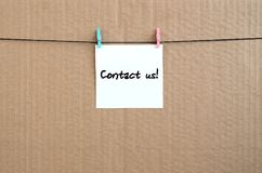 Contact us! Note is written on a white sticker that hangs with a. Clothespin on a rope on a background of brown cardboard stock images