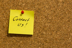 Contact us post-it note. Pinned to a noticeboard Royalty Free Stock Photo