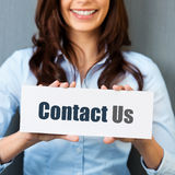 Contact us. Smiling woman showing white card with Contact us word in a close up shot Stock Photo