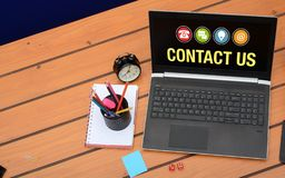 Contact us theme with laptop screen on wooden background stock photos