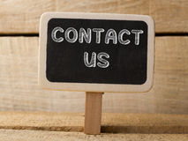 Contact us wooden sign on wood background Stock Images