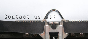 Contact us. At words written at a vintage typewriter as a communication concept stock photography