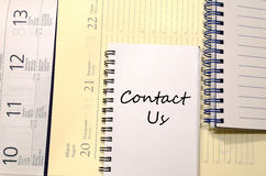 Contact us write on notebook Royalty Free Stock Photos