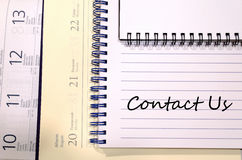 Contact us write on notebook Stock Photos