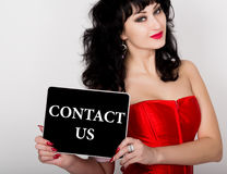 Contact us written on virtual screen. technology, internet and networking concept. sexy woman in a red corset holding pc Stock Photos