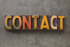 Contact word in wood type. Contact word in vintage letterpress wood type blocks against grunge metal background royalty free stock images