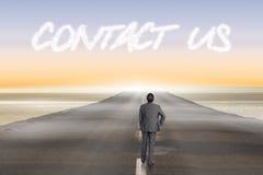 Contacte-nos contra a estrada que conduz para fora ao horizonte Imagens de Stock