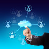 Contacting Office Workers Via The Cloud. Arm in business suit contacting two male and two female office workers via the cloud. Metaphor for cloud sourcing Royalty Free Stock Photography