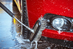 Contactless car wash self-service. Young man washing his car Stock Images