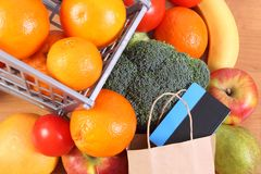 Contactless credit card, paper bag and fruits with vegetables, cashless paying for shopping. Contactless credit card with paper shopping bag, fresh fruits and Royalty Free Stock Images