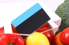 Contactless credit card, paper bag with fruits and vegetables, cashless paying for shopping. Contactless credit card and paper bag with fresh fruits and Royalty Free Stock Photo