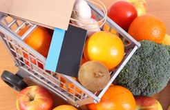 Contactless credit card, paper shopping bag and fresh fruits with vegetables, cashless paying for shopping. Contactless credit card with paper shopping bag Stock Images