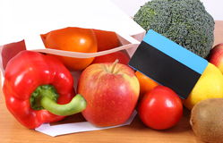 Contactless credit card, paper shopping bag with fruits and vegetables, cashless paying for shopping. Contactless credit card and paper shopping bag with fresh Royalty Free Stock Photo