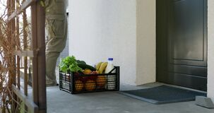 contactless delivery - delivery man leaves grocery box at the home door