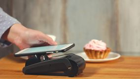 Contactless payment for dessert and coffee with the help of a male mobile phone stock video