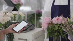 Contactless payment, in flower shop buyer uses mobile phone paying on terminal bouquet of flowers, small business
