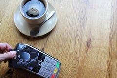 Contactless utrymme för kopia för bakgrund för betalningkortpdq med den hållande kreditkorten för hand som betalar Arkivfoto